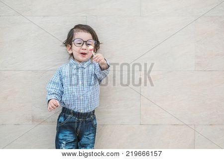 Closeup happy asian kid with eyeglasses show candy in his hand on marble stone wall textured background with copy space