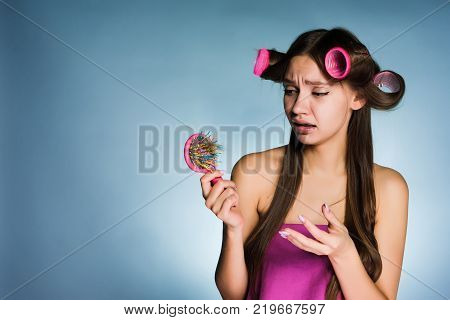 young sad girl loses her hair, holds a hairbrush, on her head curlers