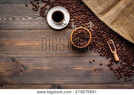 Coffee concept. Roasted beans and cup of espresso on dark wooden background top view.