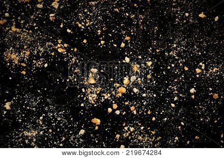 Oat cookies crumbs on black tablecloth as background