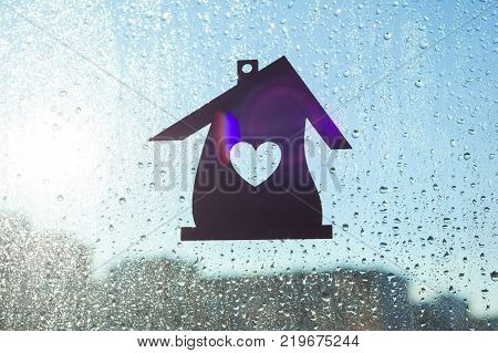 Home Sweet Home. Home symbol with a heart shape on a window background with sunny drops of rain