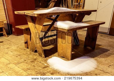 A snow covered table and bank in a winter room of an unmanned Swiss Chalet in the Alps. This is nearby the