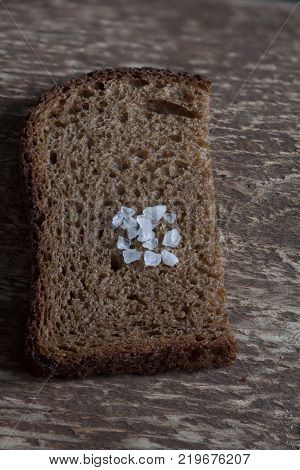 piece rough rye bread with coarse salt on a wooden background macro shot