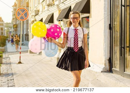 Girl teen high school student with balloons, in school uniform with glasses goes along the city street. Start of classes.