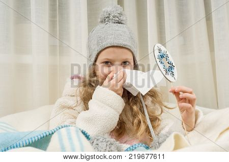 Kid girl sneezes in a handkerchief at home, The season is autumn winter.