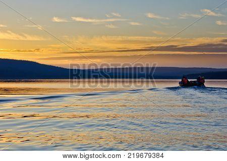 Sunset at the lake. Tourists on catamaran