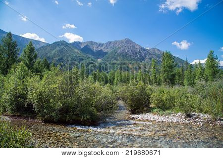 Mountain view with small river in front, sunny summer day. East Sayan, Buryatia, Russia
