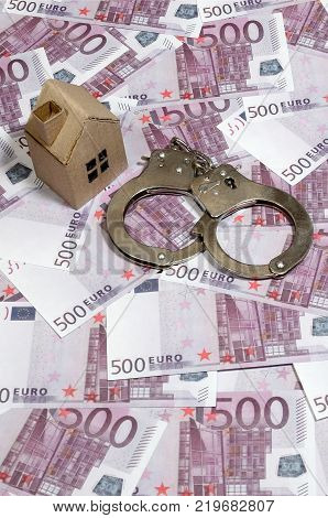 Scam with real estate. Cheating when buying or renting a house. Punishment for deception. A toy house with handcuffs on a many 500 purple euro banknotes