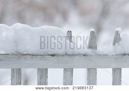 Old white wooden wood fence covered with fresh snow on winter season. Seasonal specific.