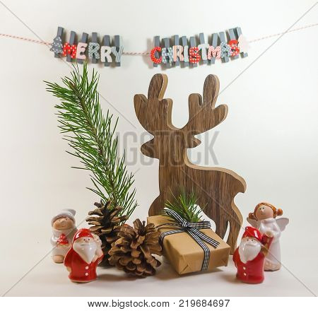 Christmas scene background with deer in woood and branch of pine small angel dolls and santaclause dry pine and gift box white background and blur alphabets.