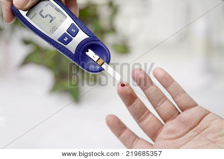 A medical test checking a drop of blood on the sugar level. Pierce the finger with a lancet.
