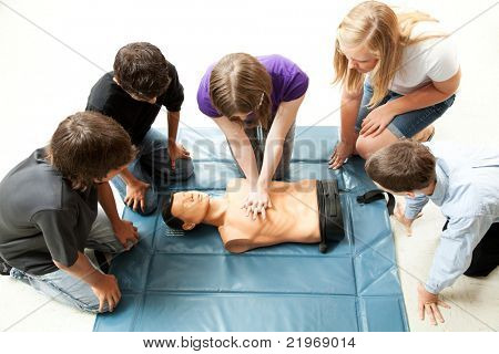Teenage students use a mannequin to practice life saving techniques.