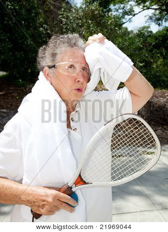 Active senior woman takes a break from racquetball to towel herself off.