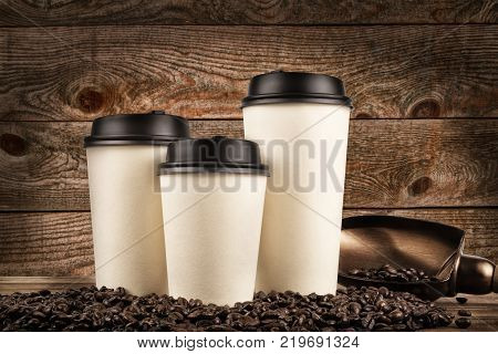 Cups of coffee and coffee beans on old wooden background.