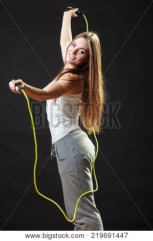 Young fit slim woman spend actively free time. Beauty happy girl wearing sports clothes with jumping skipping rope on black background.