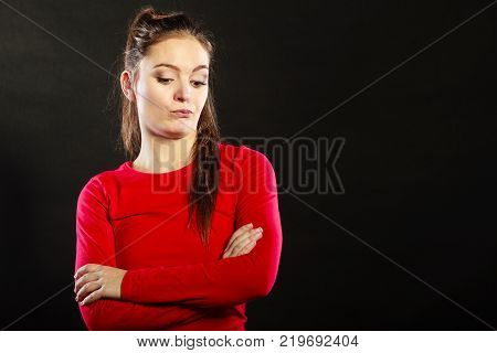 Portrait of pensive thoughtful woman. Attractive young girl thinking in studio on black.