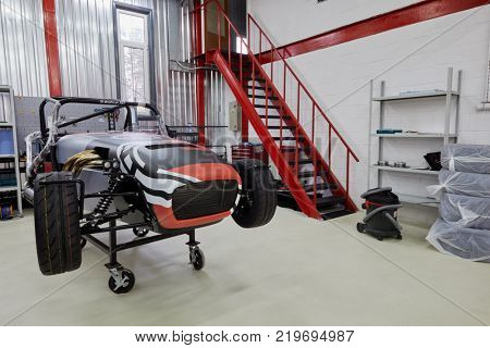 MOSCOW, RUSSIA - OCT 27, 2017: (PR) Garage of DB 527 company producer of russian sports cars with racing car on wheeled rack based on Lotus Seven.