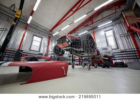 MOSCOW, RUSSIA - OCT 27, 2017: (PR) Man works with racing car on wheeled rack based on Lotus Seven in garage of DB 527 company producer of russian sports cars .