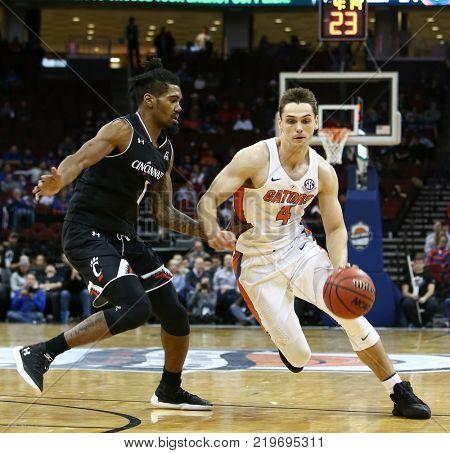 NEWARK, NJ - DEC 9: Florida Gators forward Egor Koulechov (4) dribbles the ball as Cincinnati Bearcats Jacob Evans III (1) defends on December 9, 2017 at the Prudential Center on  Newark, New Jersey.