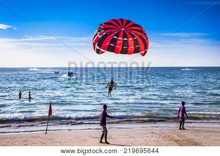 PHUKET, THAILAND - JAN 23, 2016: Tourists playing parasailing on Patong beach in Phuket on Jan 23, 2016, Thailand. Patong is a beach resort town on the west coast of Phuket Island.
