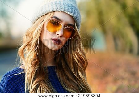 Modern young woman wearing warm clothes posing in the autumn park. Autumn fashion.