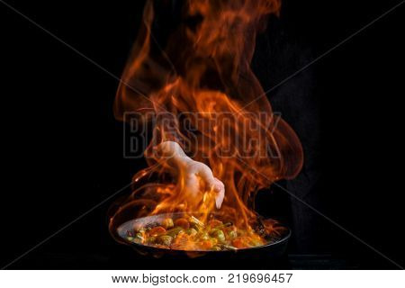 Chef is stirring vegetables in wok with fire. Dark black background.