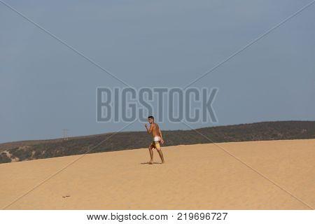 PRAIA DA BORDEIRA, PORTUGAL - AUGUST 20, 2017: Man at the dunes of the famous beach of Praia da Bordeira. This beach is a part of famous tourist region of Algarve.