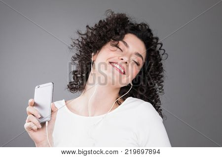Portrait of happy woman listening music in headphones on gray background with copy space