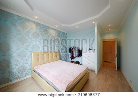 Room with double bed and clothes rack.