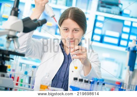 Girl laboratory assistant in the chemical laboratory of the university experiment with chemical reagents