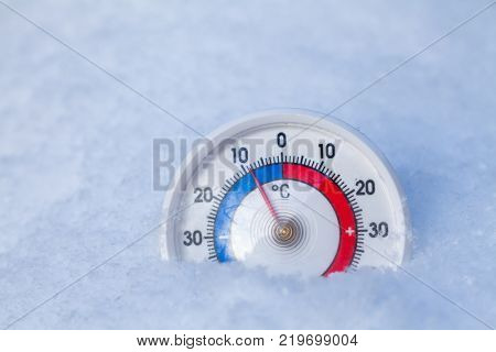 Thermometer with celsius scale placed in a fresh snow showing sub-zero temperature minus nine degree a cold winter weather concept