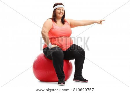 Overweight woman sitting on a pilates ball and pointing isolated on white background