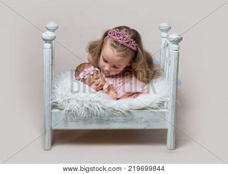 Little girl with her cute newborn sleeping sister