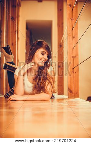 Happy cute pretty gorgeous woman laying on floor at home. Attractive young girl with long hair wearing white shirt and jeans. Instagram filter.