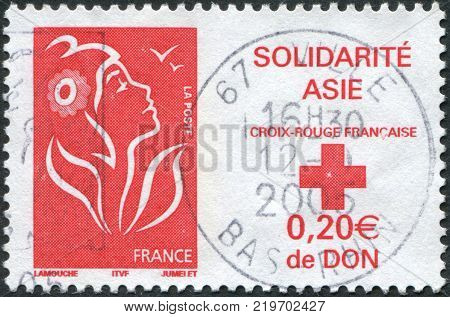 FRANCE - CIRCA 2005: A stamp printed in France Tsunami Victim Relief shows a national symbol Marianne de Lamouche and emblem of the Red Cross circa 2005