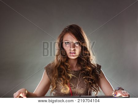 Portrait of mysterious enigmatic woman in studio on grey. Young intriguing attractive girl with long curly hair. Shining light.