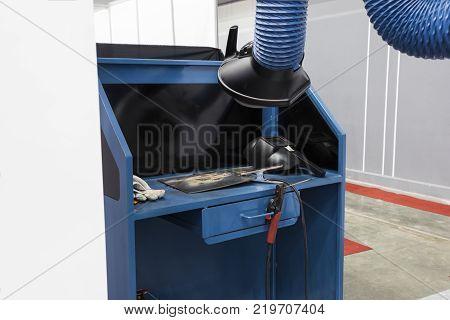 Industrial welding equipment workshop with welding fume and dust extractor.
