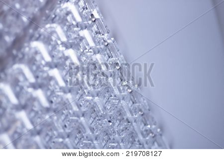 Abstract high-tech background. A sheet of transparent plastic or glass with the cut out holes. Laser cutting of plexiglass.