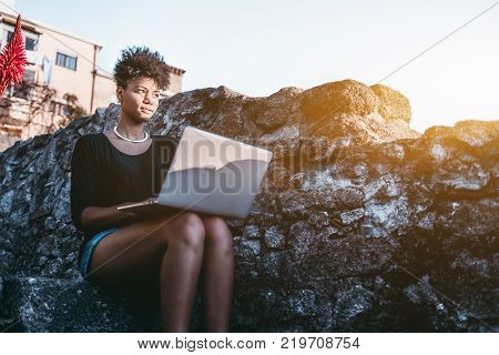 Young glamorous black female student is sitting outdoors on the step of stone staircase of her university campus with laptop while making homework and looking on a beautiful sunset