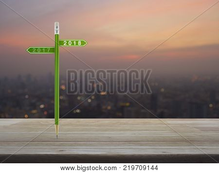 2018 and 2017 direction sign plate with green pencil on wooden table over blur of cityscape on warm light sundown Business happy new year planning concept