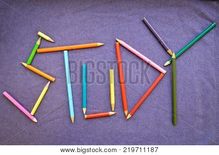 Write a study written in colored pencils. The inscription study is made up of colored pencils. The word study is composed of colored multicolored pencils on a purple background.