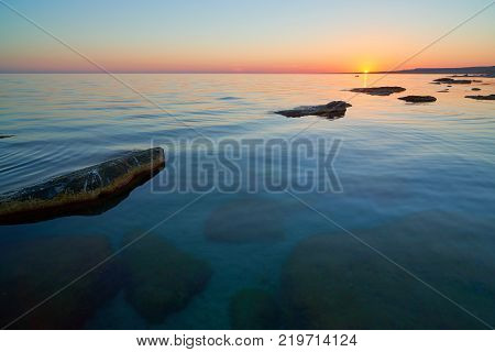 Coast of the sea with stones at sunset. On the shore of the Caspian Sea. The Caspian Sea is the largest enclosed inland water body on Earth by area.