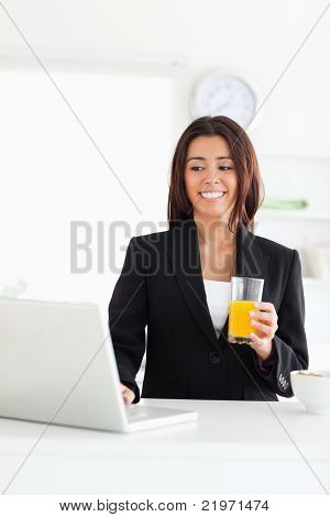 Attractive Woman In Suit Relaxing With Her Laptop While Holding A Glass Of Orange Juice