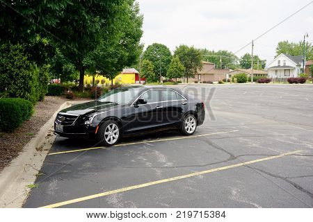 JOLIET, ILLINOIS / UNITED STATES - JULY 26, 2017: A black Cadillac sedan is parked in the parking lot of the University of Saint Francis.