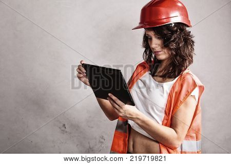 Sex equality and feminism. Sexy girl in workwear safety helmet and orange vest using tablet touchpad. Attractive woman as construction worker. Technology.
