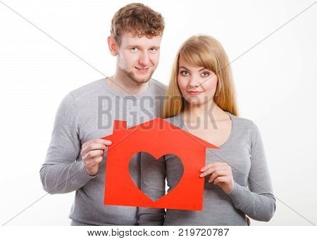 People fresh start real estate and love concept. Young enjoyable enamoured marriage holding red house with big heart.