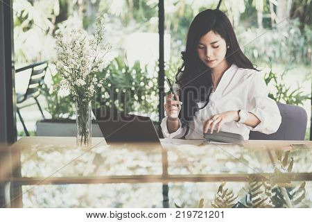 asian businesswoman holding pen with notebook at workplace. startup woman working with business plan report document at office. young female entrepreneur analyze accounting market data. financial adviser with paperwork on table.