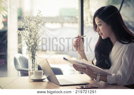 asian businesswoman analyze market chart at workplace. young female entrepreneur woman working with business document at office. analytic financial accounting plan report. paperwork on table.