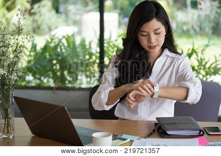 asian businesswoman look at her watch at workplace. startup woman check time on wristwatch at office. young female entrepreneur with paperwork on table.