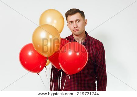 Handsome caucasian smiling fun young happy man 25-30 years in red plaid shirt with yellow golden balloons celebrating birthday on white background isolated for advertisement. Holiday party concept